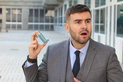 Asthmatic businessman using an inhaler at work.  royalty free stock photos