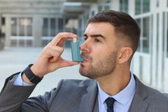 Asthmatic businessman using an inhaler at work.  stock photo