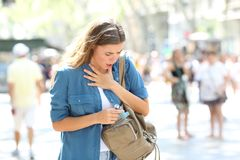 Asthmatic girl suffering an attack and searching inhaler. Asthmatic girl suffering an attack and searching the inhaler in a bag in the street stock photo