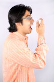 Asthmatic Patient. A portrait of an asthmatic young Indian guy inhaling an asthma medicine pump stock photography