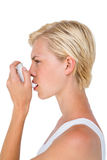 Asthmatic pretty blonde woman using inhaler. On white background stock photo