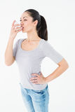 Asthmatic pretty brunette using inhaler. On white background royalty free stock image