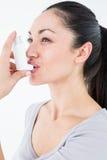 Asthmatic pretty brunette using inhaler. On white background stock photo