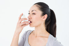 Asthmatic pretty brunette using inhaler Royalty Free Stock Photo