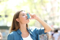 Asthmatic woman using inhaler standing in the street. Asthmatic woman having an attack using asthma inhaler standing in the street stock photo