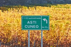 Asti Cuneo motorway street sign and vineyard in autumn in Italy. Asti Cuneo motorway street sign and vineyard in autumn with yellow leaves in a sunny day in Royalty Free Stock Images