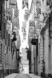 Asti (Italy). Asti (Piedmont, Italy): historic street with flags for the medieval Palio. Black and white Royalty Free Stock Photos