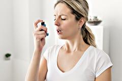 Astmatisch gebruikend haar inhaleertoestel wegens ademmoeilijkheden stock afbeelding