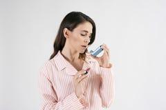 Astmatyczna kobieta używa astma inhalator podczas astma ataków zdjęcia stock