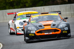 Aston Martin race car. An Aston Martin race car leads a Porsche GT3 at the Highlands Park track in New Zealand Royalty Free Stock Image