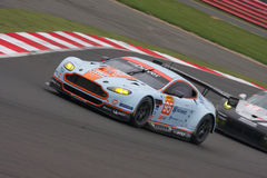 Aston Martin V8 Vantage GTE AM competing at the 6 Hours of Silverstone. Aston Martin leads a Porsche 911 RSR through the bends at Silverstone 2014 stock image