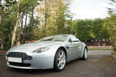 Aston Martin Vantage GT. Silver (or white) Aston Martin Vantage Grand Tourer or GT on roadway surrounded by trees Stock Images