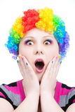 Astonish clown with rainbow make up. Beautiful woman in rainbow clown wig with freckles and creative rainbow make-up in astonishment at white background Stock Images