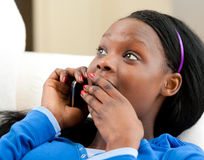 Astonished afro-american teenager talking on phone Royalty Free Stock Image