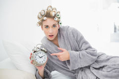 Astonished blonde woman in hair curlers pointing her alarm clock Royalty Free Stock Photos