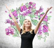 An astonished blonde woman with hands up and she is dreaming about summer flowers. The sketch of purple flowers is drawn on the co Royalty Free Stock Photos