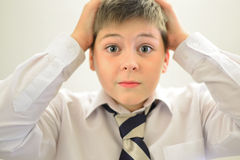 Astonished boy holding his hands behind  head Royalty Free Stock Photo