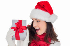 Astonished brunette in santa hat showing gift Stock Photography