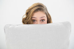 Astonished brunette woman hiding her face behind a white pillow Royalty Free Stock Images