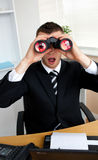 Astonished businessman looking through binoculars Stock Image