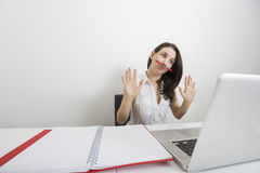 Astonished businesswoman looking at laptop while holding pen under nose in office Royalty Free Stock Photo