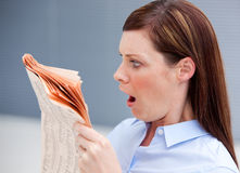 Astonished businesswoman reading newspaper. In her office Stock Photography