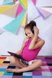 Astonished child girl with a tablet in the room. The concept of stock images
