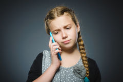 Astonished cute girl with cell phone. isolated on gray Royalty Free Stock Photo