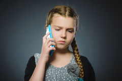 Astonished cute girl with cell phone. isolated on gray Royalty Free Stock Photography