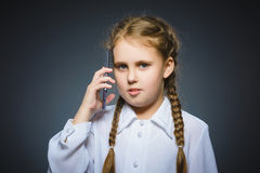 Astonished cute girl with cell phone. isolated on gray Stock Photography