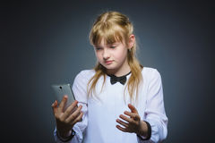 Astonished cute girl with cell phone. isolated on gray Royalty Free Stock Images