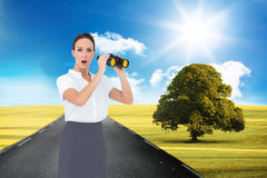 Astonished elegant businesswoman holding binoculars Stock Image