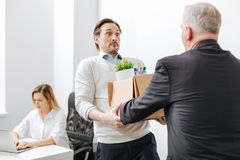 Astonished employee receiving the box with belongings from the employer. Full of frustration. Frustrated puzzled shocked employee standing and getting the box Royalty Free Stock Image