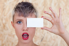 Astonished girl with business card near eye Stock Images