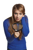 Surprised woman looking through the magnifying glass downwards Royalty Free Stock Photos