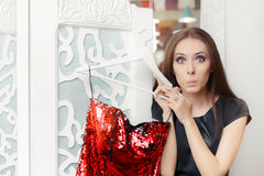 Astonished Girl Trying on Red Party Dress in Dressing Room Royalty Free Stock Photos