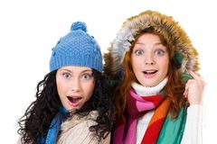Astonished girls. Two friends in warm knitted clothes looking at camera over snowflake background Stock Image