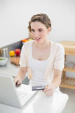 Astonished gorgeous woman using her notebook for home shopping in her kitchen Stock Image