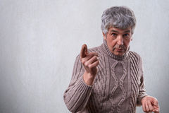 An astonished handsome elderly man with gray hair dressed in sweater standing near white wall pointing with finger wanting to say. Something important. Senior Stock Photo