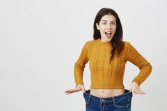 Astonished and happy young lady being impressed and excited because of losing weight, showing empty space in jeans by. Stretching it, standing over gray royalty free stock image