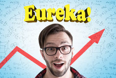 Astonished hipster guy, eureka, blue wall Stock Photography