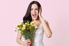 Astonished impressed young lady stands isolated over pink background, opens mouth widely in surprise, holding bouquet of spring. Flowers, looks happy. Copy stock photos