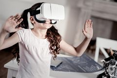 Astonished laughing girl seeing unbelievable VR image. Future is here. Surprised smiling pretty girl exploring new world by wearing VR glasses standing in the royalty free stock photos