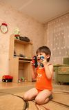 Astonished little boy on the floor. Little boy in nursery room sitting on the floor and watching animation Royalty Free Stock Photo