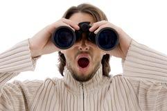 Astonished male watching through binocular Royalty Free Stock Images