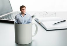 Astonished man in cup. On the background of desktop stock photo