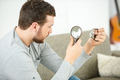 Astonished man looking through magnifying glass Royalty Free Stock Images