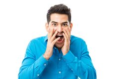Astonished Man With Mouth Wide Open Over White Background. Astonished young man with mouth wide open standing over white background stock image