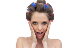 Astonished model in hair rollers posing. Astonished young model in hair rollers posing on white background Royalty Free Stock Photography