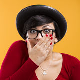 Astonished nerd girl. Beautiful girl with a astonished expression, wearing a hat and nerd glasses over a yellow background Stock Image